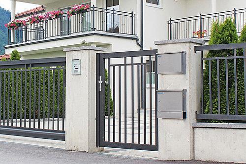 Schiebetor und Gartentür aus Aluminium in anthrazit vor einer Hauseinfahrt