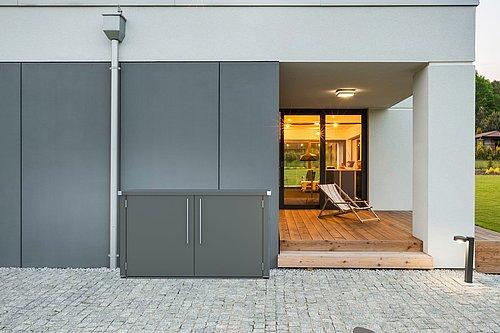 Die Abfallbox Big Wasty als Mülltonnenverkleidung von Guardi in anthrazit, steht genau vor einer grauen Hausmauer, daneben fängt der Terrassenboden in Holzoptik an