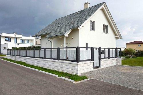 Kombinierter Einzelstabzaun aus Aluminium in anthrazit mit grauer Lochblechfüllung, Modell Loskana von GUARDI, vor weißem Einfamilienhaus