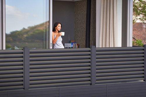 Blickdichtes Balkongeländer vom Modell Plissée in anthrazit, dahinter steht eine halb zu sehende Frau mit einer Kaffeetasse in der Hand