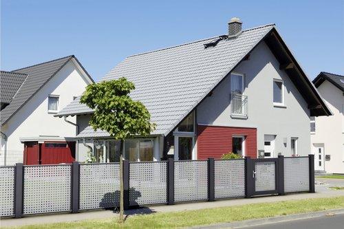Architektonischer Lochblechzaun in grau mit schwarzen Stehern, mit passender Gartentüre, Modell Loos von GUARDI, vor grauem Haus