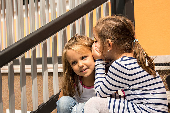 Zwei Kinder sitzen vor einem Geländer, das eine flüstert dem anderen etwas ins Ohr