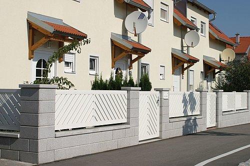 Aluminiumzaun in weiß, Modell Umbria von Guardi mit Gehtür, doppelt-diagonal A-Form, dahinter ein weißes Reihenhaus