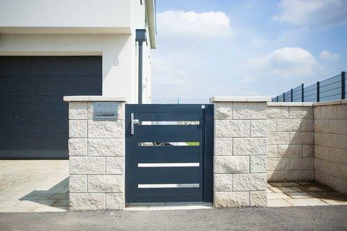 Gartentüre aus Latten in anthrazit, Modell Triest, integriert in Steinmauer, Garage im Hintergrund