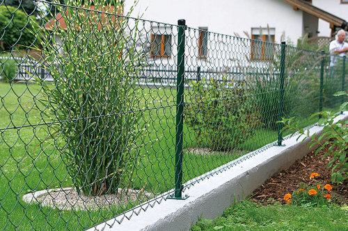 Maschendrahtzaun in grün auf einem betonfundament, dahinter ist eine grüne wiese mit sträuchern