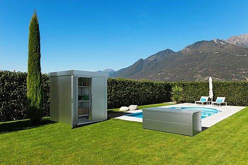 Gartenhaus mit Doppelflügeltor und Gartenbox von Guardi in silber-metallic stehen auf der Wiese, dahinter sind Tujen und ein Pool zu sehen