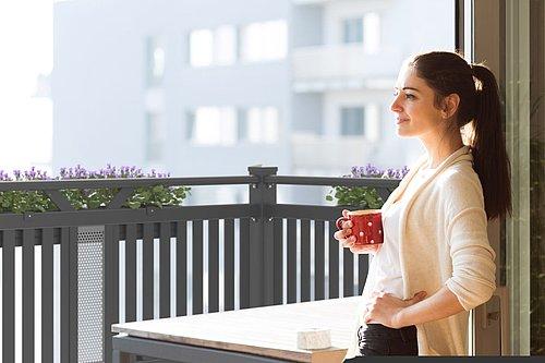 Balkon aus Aluminium mit dem Modell Schladming als Sichtschutz in graud, im Vordergrund steht eine Frau und lehnt sich an die Wand mit einer Tasse in der Hand