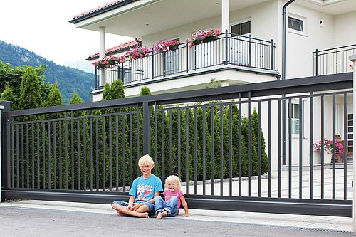 Schiebetor aus Einzelstäben in anthrazit, Modell Toskana, vor weißem Haus, zwei Kinder sitzen vor Tor