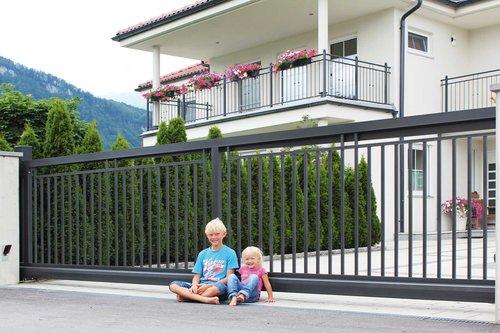 Schiebetor aus Einzelstäben in anthrazit, Modell Toskana von GUARDI, vor weißem Haus, zwei Kinder sitzen vor dem Tor