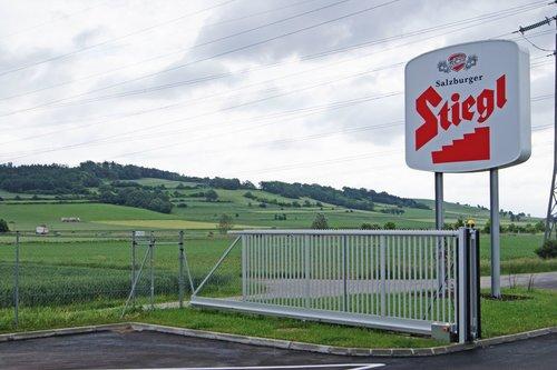 Industrieschiebetore in grau vor einer großen firmeneinfahrt, das firmenlogo prangert präsent im bild, weite landschaft ist im hintergrund zu sehen