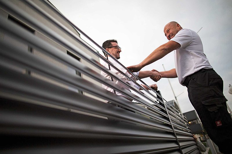 GUARDI Mitarbeiter reicht einem Kunden über einen Aluminiumzaun hinweg die Hand